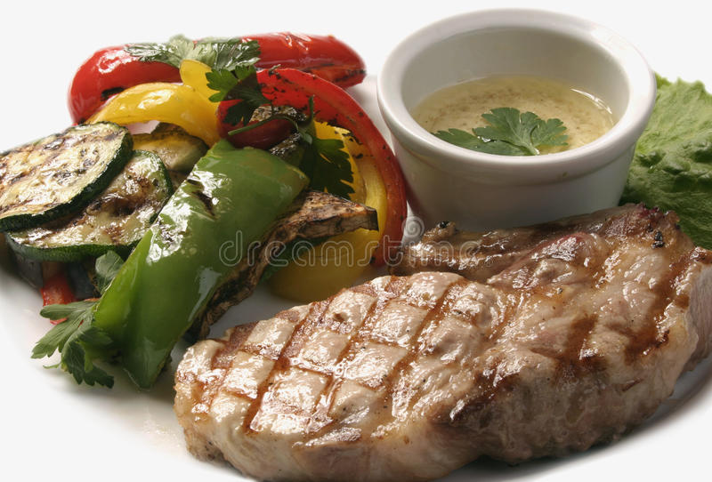 Steak. Grilled pork steak with vegetables and white sauce stock photography