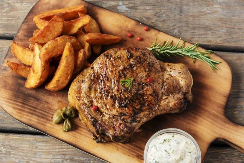 Steak auf dem Knochensteak mit Ofenkartoffel und Soße stockbild
