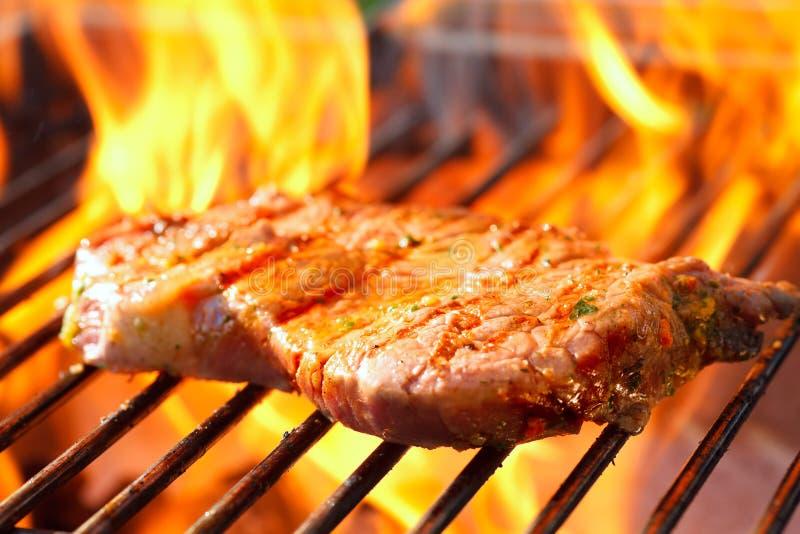 Steak auf Grill mit Flammen stockbilder