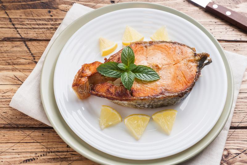 Steak baked fish salmon on a plate with lemon. Wooden table royalty free stock photography