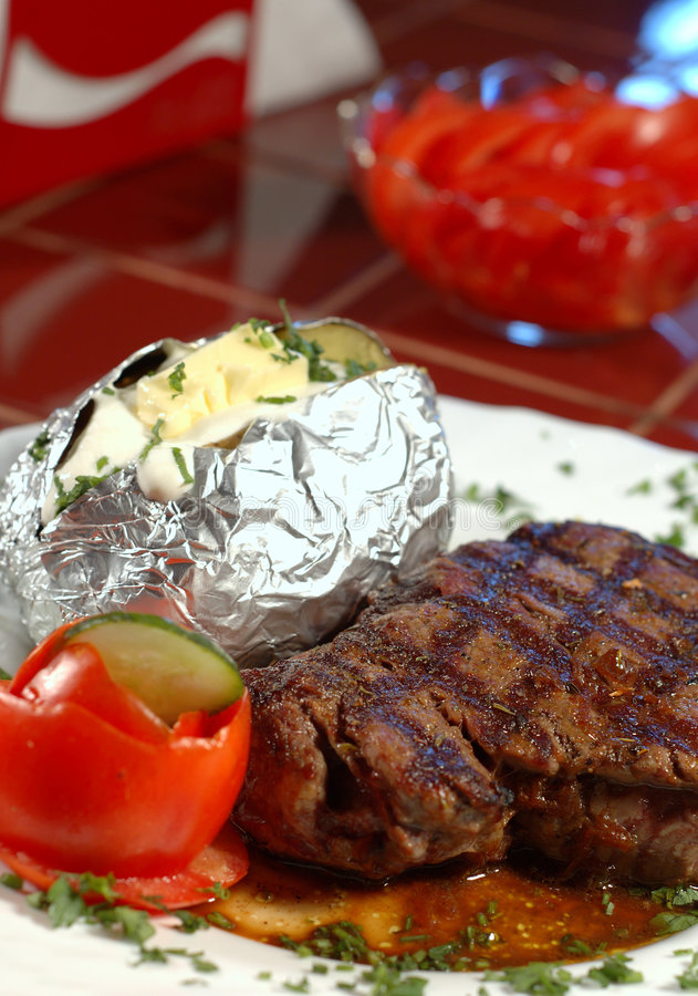 Steak and baked potatoe stock image
