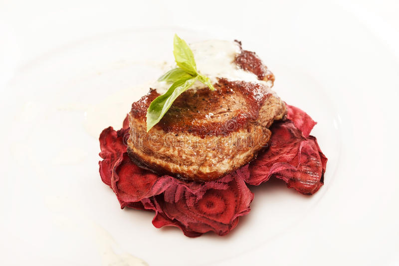 Steak on the beet chips stock image