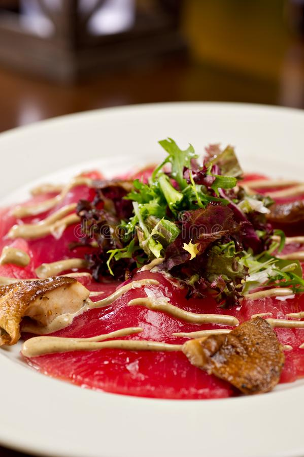Steak carpaccio with mushrooms and arugula salad stock photography