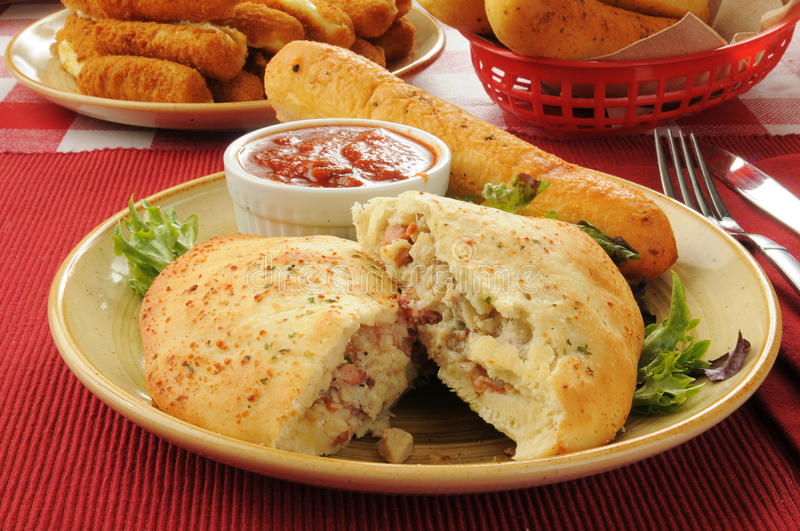 Steak and cheese calzone. With bread and mozzarella cheese sticks royalty free stock photography