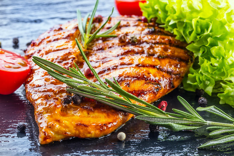 Steak chicken breast olive oil cherry tomatoes pepper and rosemary herbs. royalty free stock image