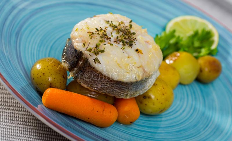 Steak of  codfish prepared and served with boiled potatoes, carrots. And greens royalty free stock image