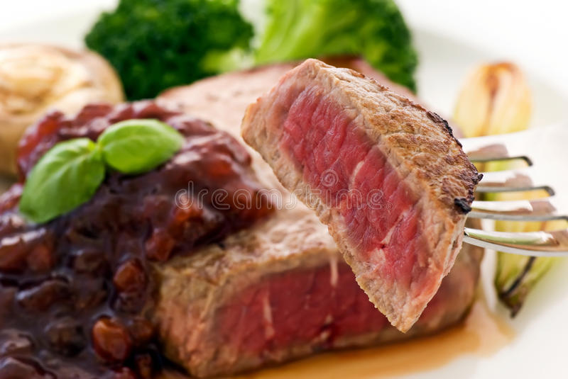 Steak with cowberry sauce. And vegetables royalty free stock photos