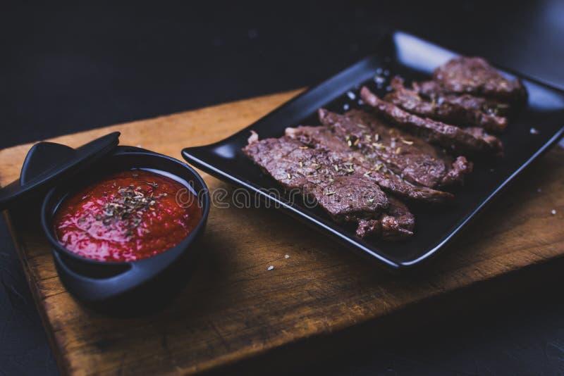 Steak de boeuf roulé à la sauce tomate sur fond noir image libre de droits