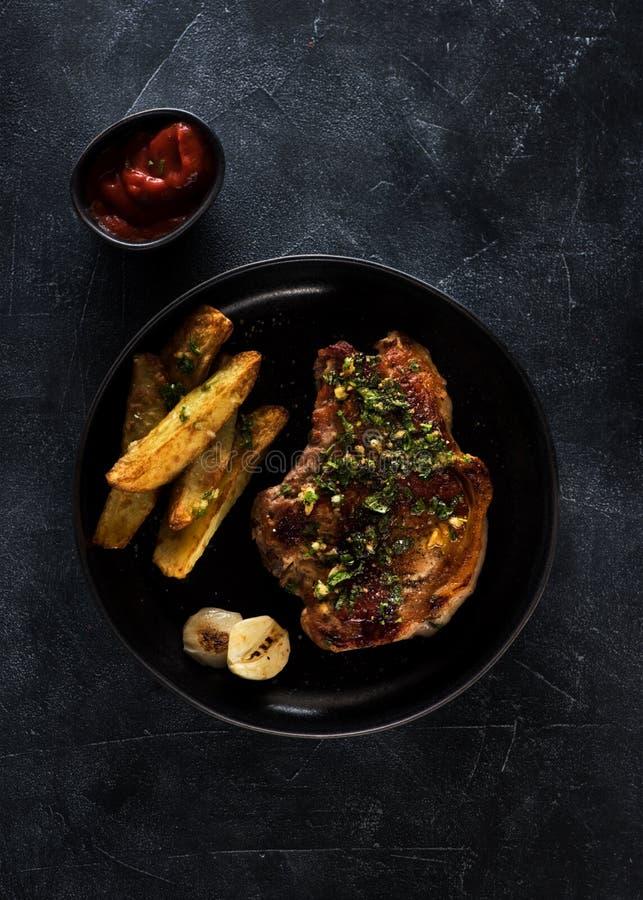 Steak des gebratenen Schweinefleisch auf einer Platte mit gebratenen Kartoffeln stockfotografie