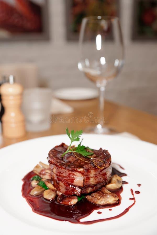 Steak des zarten Lendenstücks eingewickelt im Speck mit roter Soße lizenzfreie stockfotos