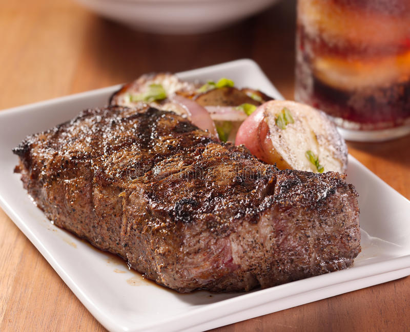Steak dinner with potatoes. Grilled steak with potatoes and cola in background stock photos