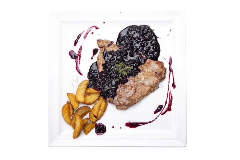 steak entrecote on pork bone with blueberry sauce. meat with berry sauce. delicious recipe. berry sauce stock photography