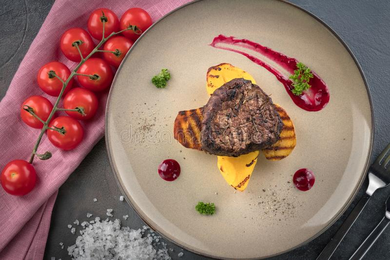 Steak Filet Mignon with Smoke. Baked Potatoes and Cranberry Sauce. Ð¡herry tomatoes. Grey background royalty free stock photos