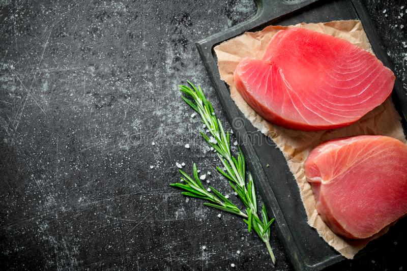 Steak of fresh raw tuna on parchment with a sprig of rosemary. On dark rustic background royalty free stock photography