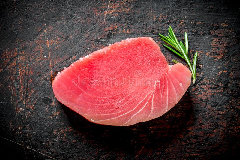 Steak of fresh raw tuna with rosemary. On dark rustic background royalty free stock image
