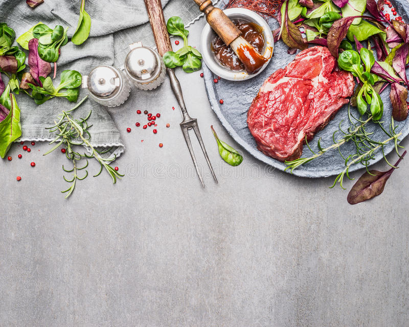 Steak and green salad. Meat preparation and marinating for grill or BBQ on gray stone background. Top view, border stock photos