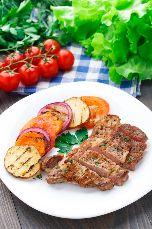 Steak with grilled vegetables on a plate stock images