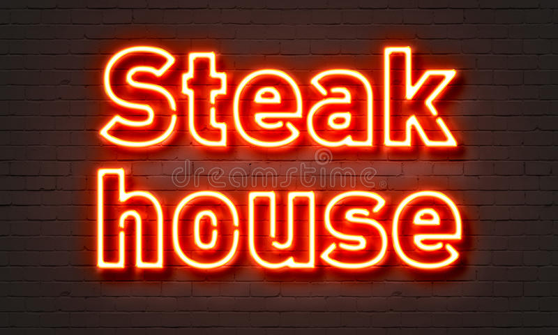 Steak house neon sign on brick wall background. Steak house neon sign on brick wall background royalty free stock photography