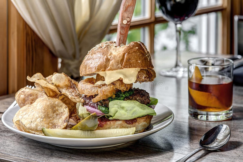 Delicious Burger with Cocktail and Wine on Table royalty free stock photography