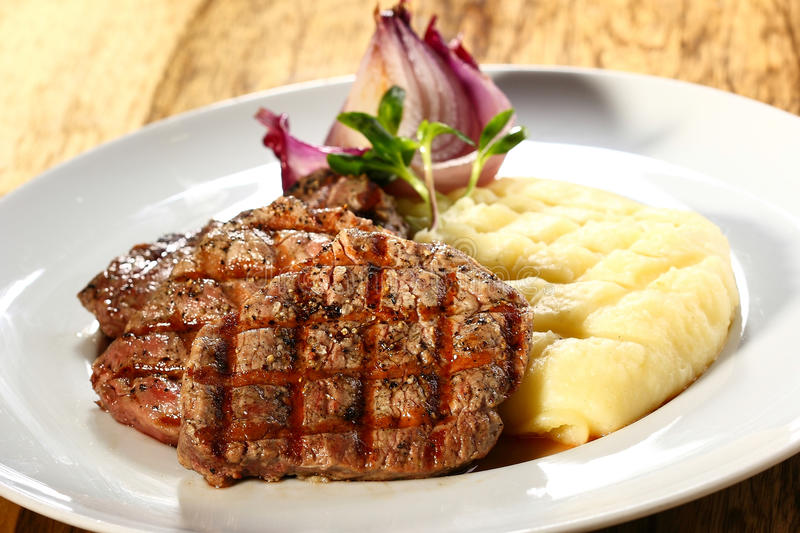 Steak and mashed potatoes. A dish of steak and mashed potatoes on a white plate royalty free stock images