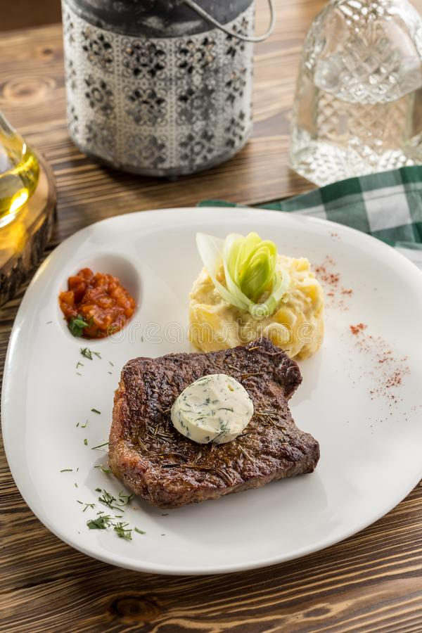 Steak with mashed potatoes and tomato sauce on wooden table stock photo