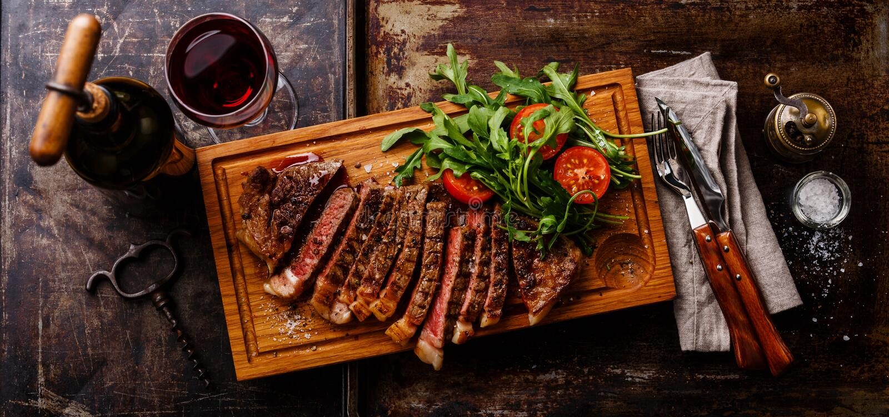 Steak mit Arugulasalat und Rotwein lizenzfreies stockfoto