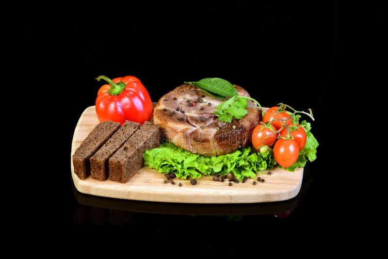 Steak mit Gemüse auf einem hölzernen hackenden Brett lizenzfreie stockfotos