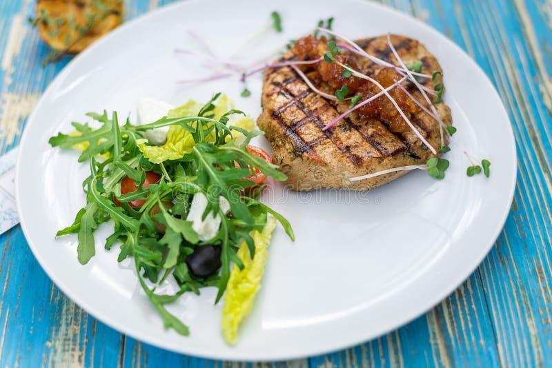Steak mit Gemüsesalat und Kräutern auf einer weißen Platte lizenzfreie stockbilder