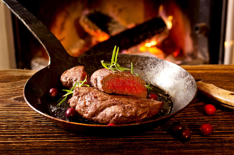 Steak in Pan mit Kamin-Feuer lizenzfreies stockfoto