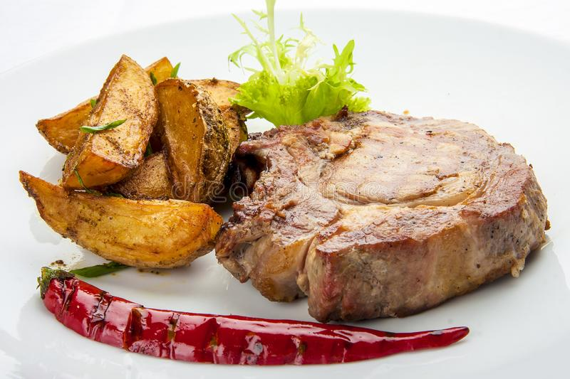 Steak from pork chop with potatoes on a white plate royalty free stock images