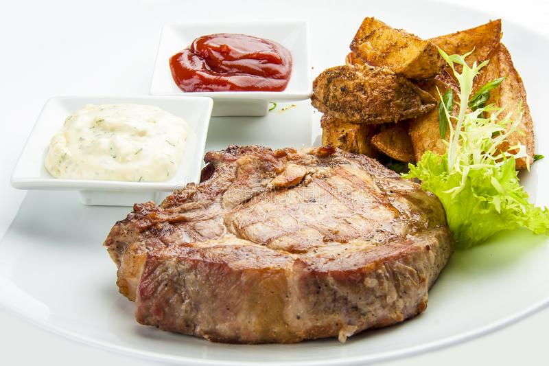 Steak from pork chop with potatoes on a white plate royalty free stock image