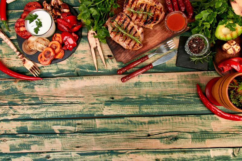 Steak pork grill on wooden cutting board with a variety of grilled vegetables stock image