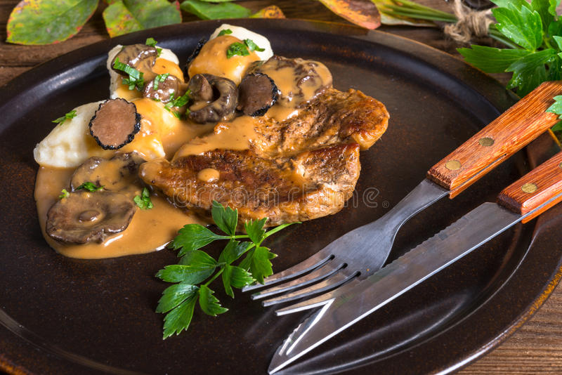 Steak with potato dumplings and forest mushroom sauce. A Steak with potato dumplings and forest mushroom sauce royalty free stock photo