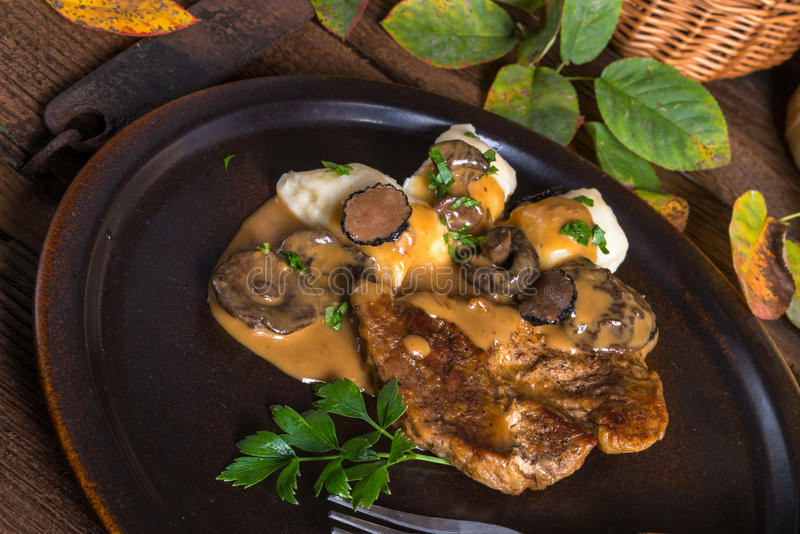 Steak with potato dumplings and forest mushroom sauce royalty free stock photo