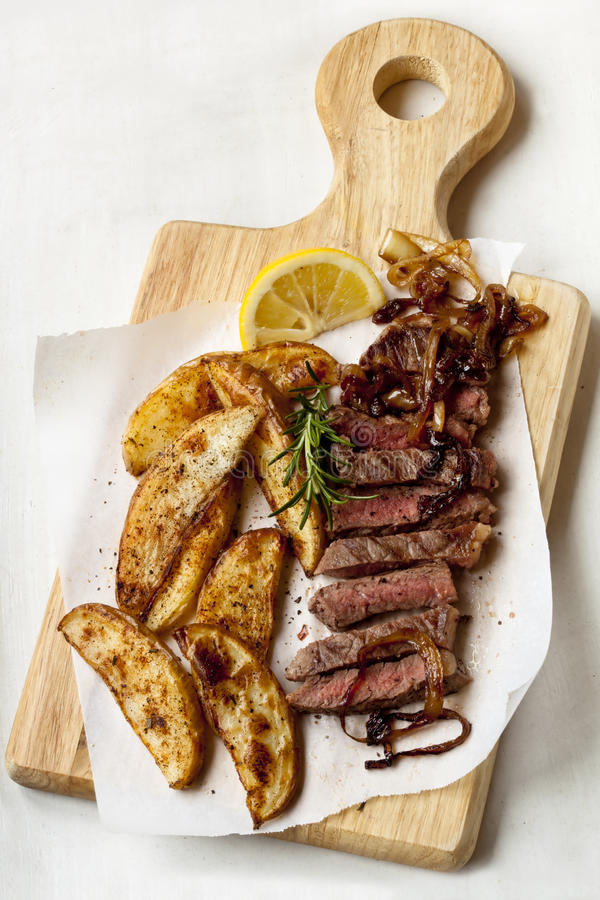 Steak and Potato Wedges. Sliced beef steak with potato wedges, onions, rosemary and lemon, on a board royalty free stock image
