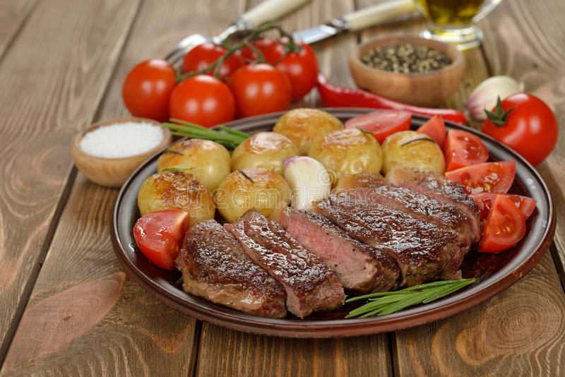 Steak with potatoes. On a brown background royalty free stock image