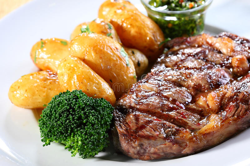 Steak and potatoes. A dish of steak and potatoes on a white plate and small salad stock photography
