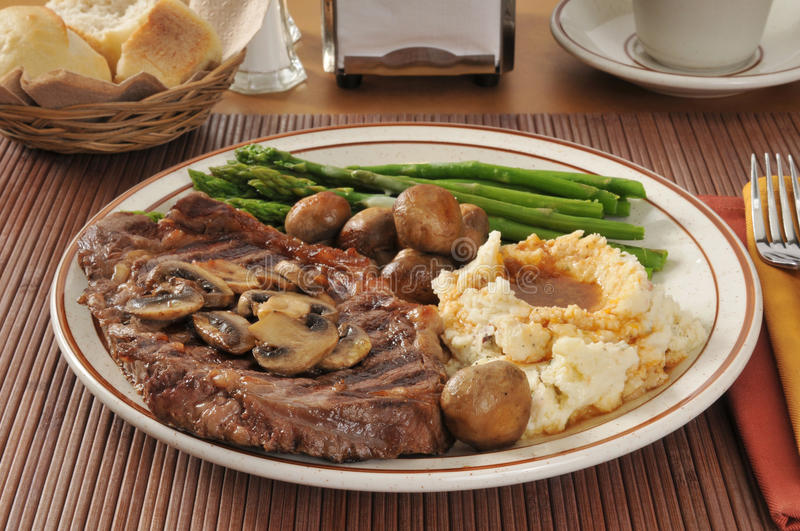 Steak and potatoes. A grilled rib steak with sauteed mushrooms, asparagus, and mashed potatoes stock photography
