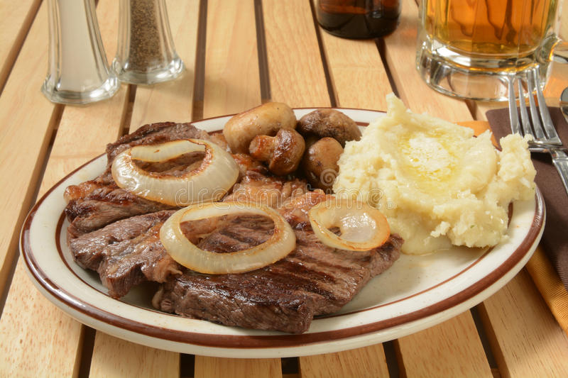 Steak and potatoes. Steak and mashed potatoes with butter and sauteed mushrooms stock image