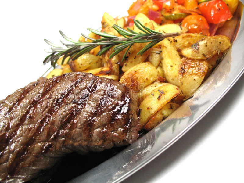 Steak, potatoes and vegetables. Tilted royalty free stock images