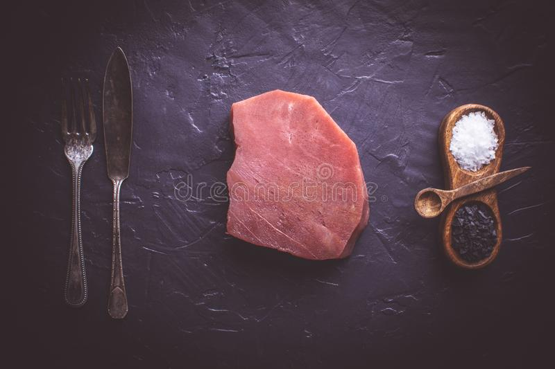Steak of Raw Tuna on Dark Stone Background. Fresh Steak of Raw Tuna on Dark Stone Background stock image