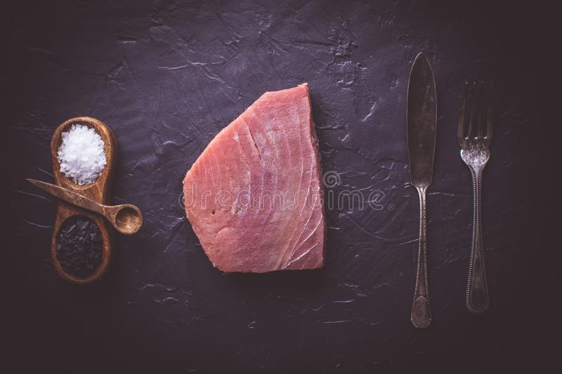 Steak of Raw Tuna on Dark Stone Background. Fresh Steak of Raw Tuna on Dark Stone Background stock images