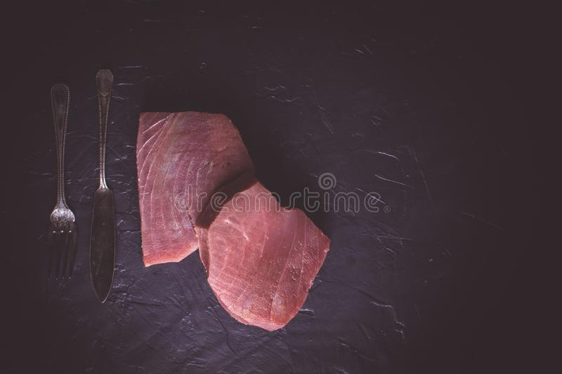 Steak of Raw Tuna on Dark Stone Background. Fresh Steak of Raw Tuna on Dark Stone Background stock photo