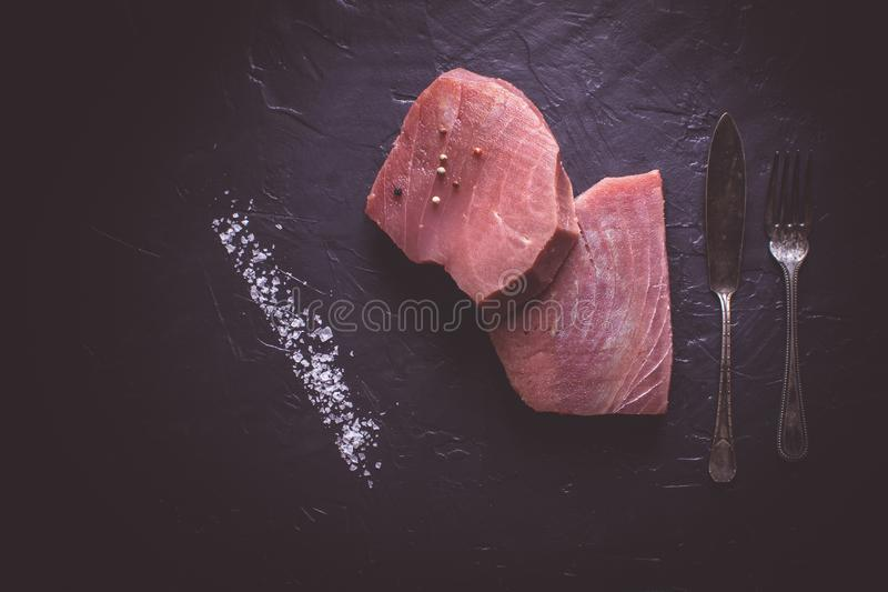 Steak of Raw Tuna on Dark Stone Background. Fresh Steak of Raw Tuna on Dark Stone Background royalty free stock images