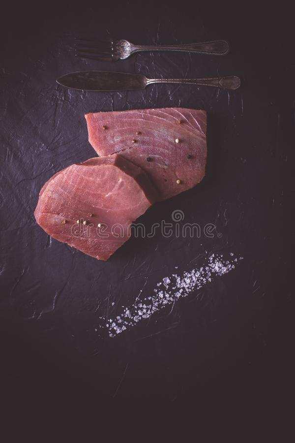 Steak of Raw Tuna on Dark Stone Background. Fresh Steak of Raw Tuna on Dark Stone Background royalty free stock photos