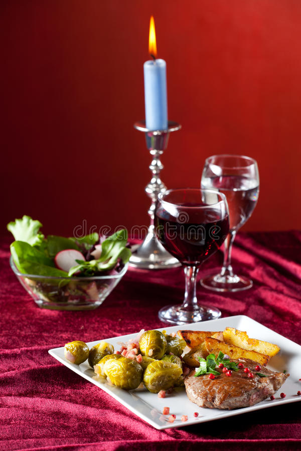 Steak with red pepper corns. And brussel sprouts royalty free stock images