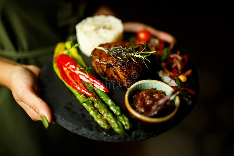 Steak with rice and vegetables on a black plate stock photos