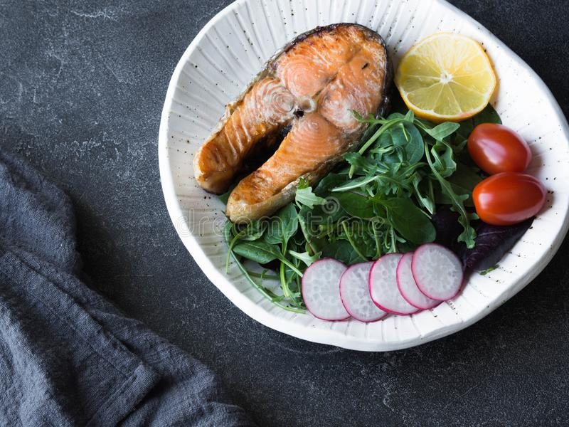Steak of roasted salmon with mix greens salad, tomatoes, radish slices and lemon royalty free stock images