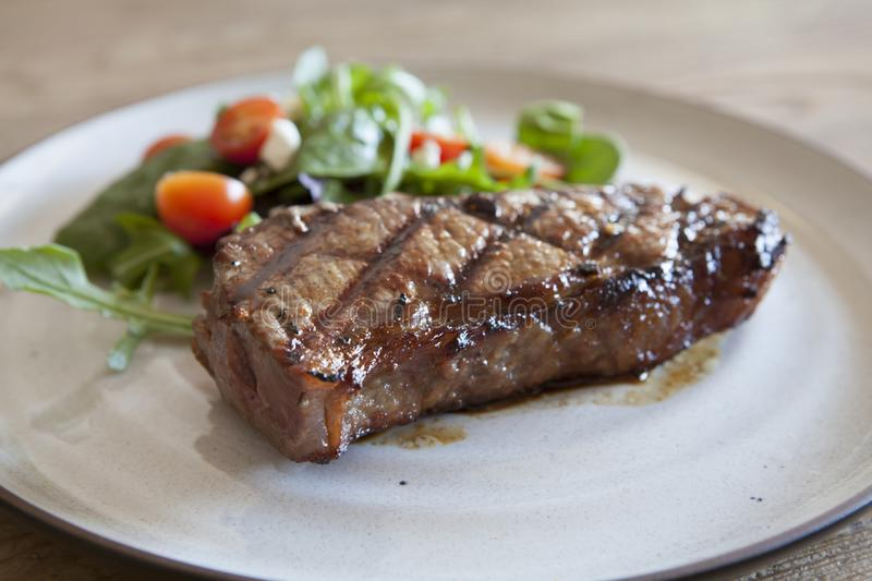 Steak and Salad. On a Wooden Background royalty free stock photo