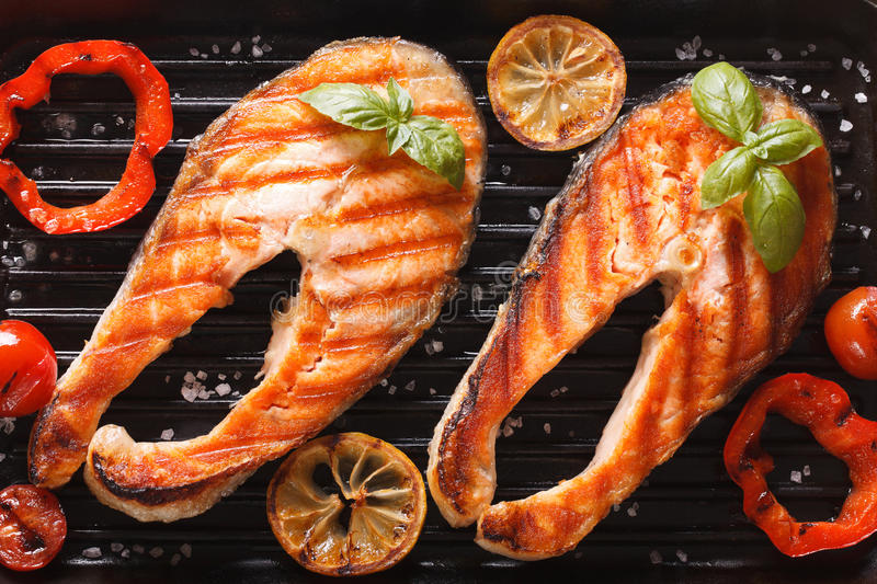 Steak salmon and vegetables on the grill. horizontal top view. Grilled red fish steak salmon and vegetables on the grill. horizontal top view close-up stock image